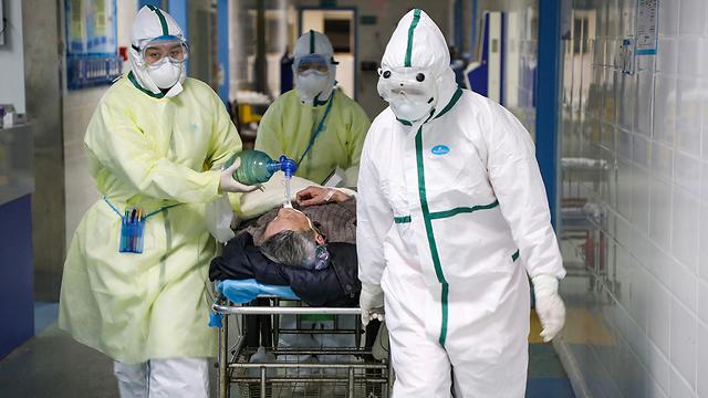 רופאים עם מסכות מובילים חולה ל בידוד ב ווהאן סין נגיף קורונה (צילום: רויטרס)