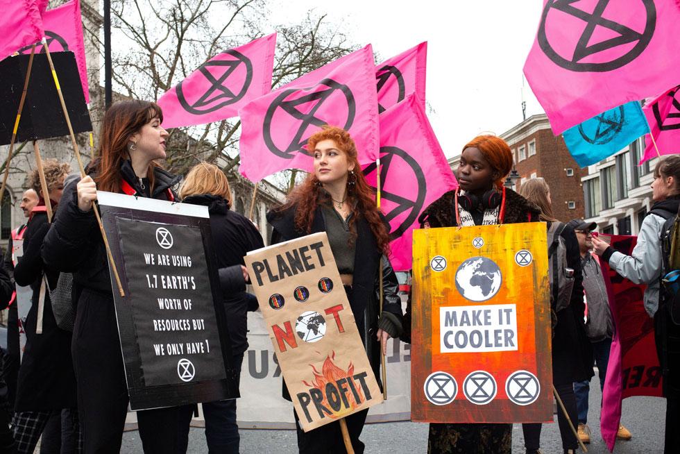 """חמושים בדגלים ורודים, יצאו מפגינים לרחובות לונדון למחות על ההרס שזורה תעשיית הטקסטיל והאופנה, מהמזהמות בעולם. הם נשאו שלטים כמו """"כדור הארץ ולא רווחים"""" בכניסה לתצוגות האופנה, מתוך מטרה לעודד את המעצבים להשתמש בחומרים ידידותיים לסביבה ולהפחית ייצור מזהם (צילום: AP)"""