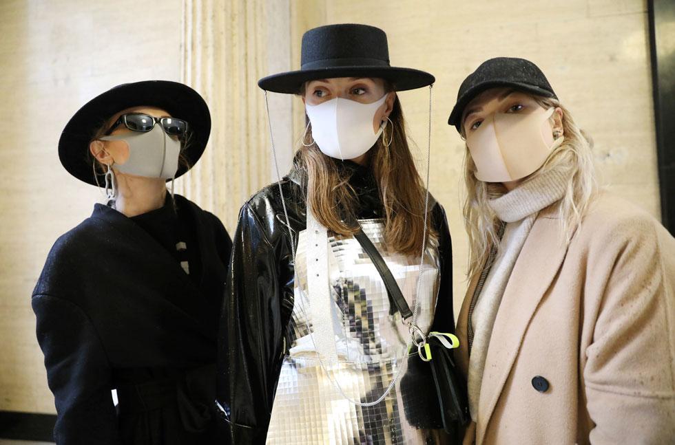 שלוש האורחות מלטביה שהתייצבו בתצוגה של המותג Fashion Scout לא פספסו הזדמנות להתייחסות אקטואלית והגיעו עם מסכות מעוצבות, שמאז בהלת וירוס הקורונה הפכו לאביזר אופנה טרנדי (צילום: AP)