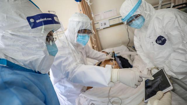 רופא בודק חולה שנדבק בנגיף הקורונה בבית חולים בווהאן (צילום: AFP)
