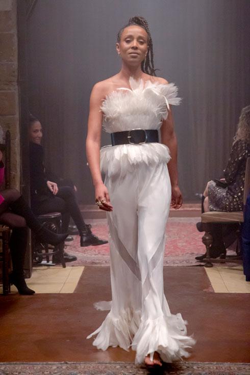 הזמרת ושחקנית אסתר רדא צעדה על המסלול במכנסיים לבנים ומחוך נוצות שהוצמד אל הטורסו באמצעות חגורת עור רחבה בצבע שחור (צילום: ענבל מרמרי)