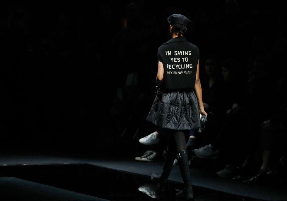 """המסרים על משבר האקלים וקיימות שהמעצב ג'ורג'יו ארמאני הציף בשבוע האופנה לגברים, המשיכו גם הפעם עם הדפסים כמו """"אני אומרת כן למיחזור"""" שהופיעו על גבן של חולצות המותג, וסיסמאות שהוצגו על מסכי לד באולם התצוגה. בקרוב בחנות המותג בישראל וברשת פקטורי 54 (צילום: AP)"""