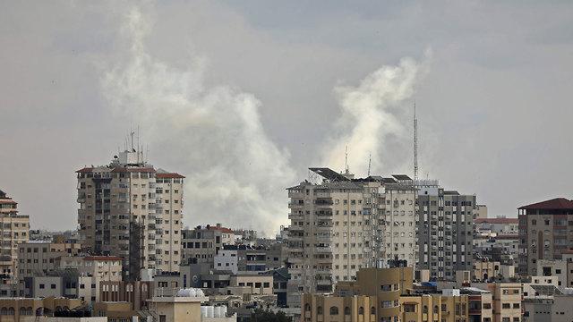 שבילי עשן מרקטות שנורו על ידי חמושים פלסטינים בעיר עזה (צילום: AFP)