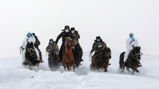 Китайская полиция сопровождает медиков при проверке в округе Алтай. Фото: EPA