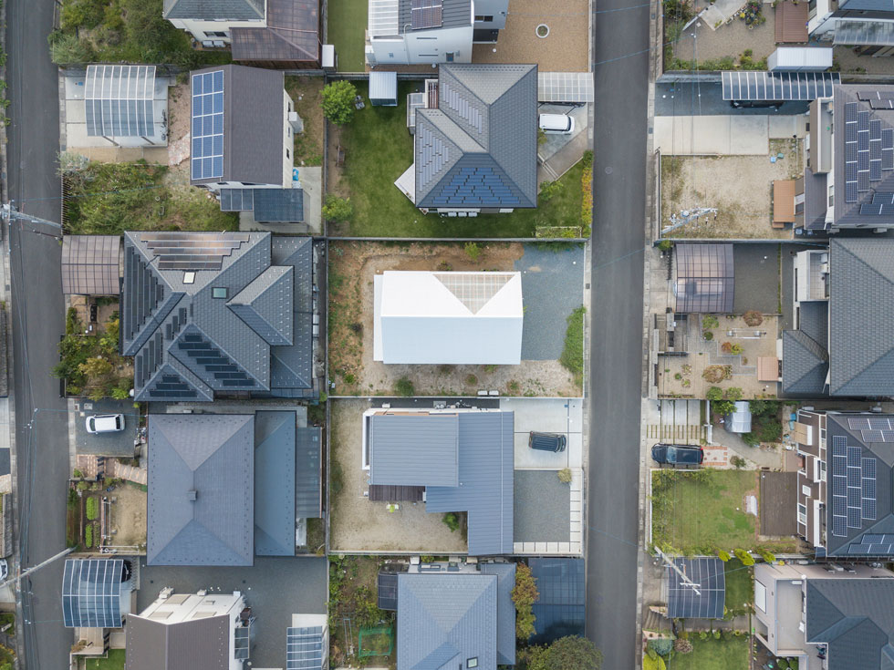 צילום רחפן מעל השכונה, החדשה יחסית, בעיירה סונובה. שימו לב לכמות הפאנלים הסולאריים על הגגות ולחדרי השמש השקופים שנבנו כתוספות. הבית החדש והבהיר במרכז נראה מבחוץ כמו תיבה פשוטה, עם רמז אחד למורכבות הפנים (צילום: shinkenchiku_sha, Yosuke Ohtake and Yohei Sasakura)