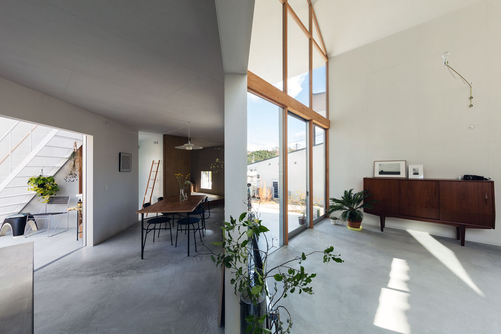 מבט מכיוון המטבח. משמאל חדר השמש, בתווך פינת האוכל, ומימין הסלון. הרהיטים מועטים, ויחד עם המנעד החומרי והצבעוני המצומם נוצרת האווירה המינימליסטית (צילום: shinkenchiku_sha, Yosuke Ohtake and Yohei Sasakura)