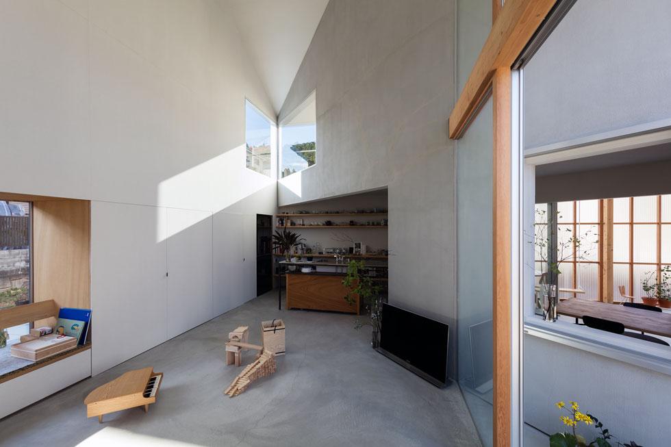 מרפסת משולשת משותפת לפינת האוכל ולסלון, וכך גם המטבח, שנפתח אל החלל הכפול. בקירות שהתקבלו בגובה 2 הקומות, הנראים מהסלון וניצבים לו בזווית של 45 מעלות, נפערו חלונות המטילים אור בצורות המעצימות את החוויה הגיאומטרית (צילום: shinkenchiku_sha, Yosuke Ohtake and Yohei Sasakura)
