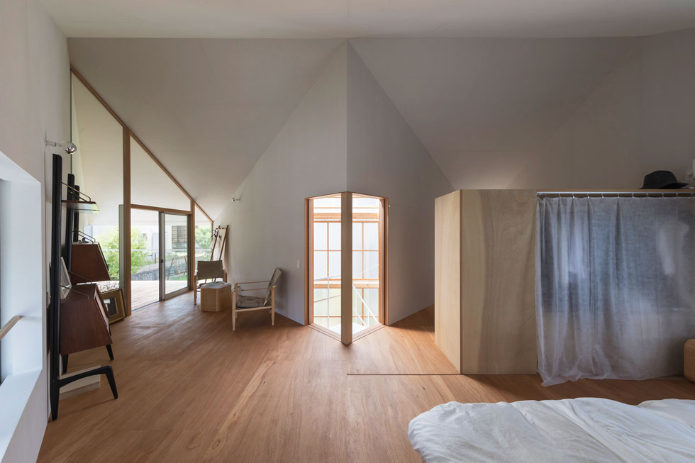 חדר השינה תופס את כל שטחה של הקומה העליונה. חלוקת הפנים למשולשים מודגשת כאן באמצעות הכניסה הכפולה, קווי הגג והמרפסת הצמודה (צילום: shinkenchiku_sha, Yosuke Ohtake and Yohei Sasakura)