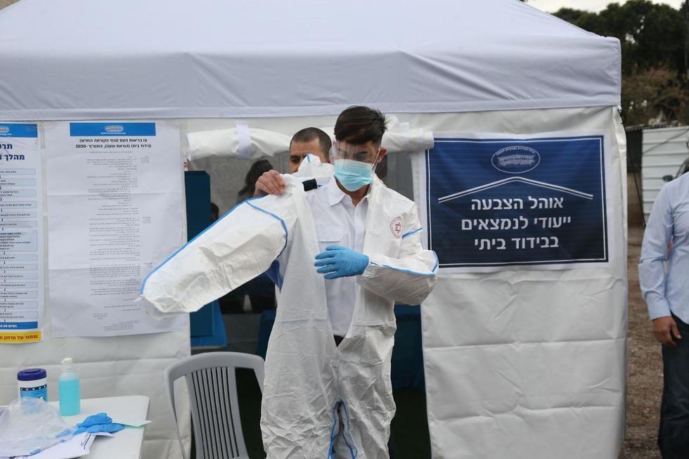 Сотрудник специального избирательного участка коронавируса. Фото: Моти Кимхи