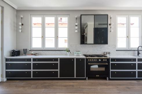 המטבח ממשיך את הקו העיצובי של פינת האוכל, בשילוב תאורה סלונית ומראה. חלקו השני של המטבח - התנורים, המקרר והמזווה - נפרד וסגור (צילום: סיון אסקיו)