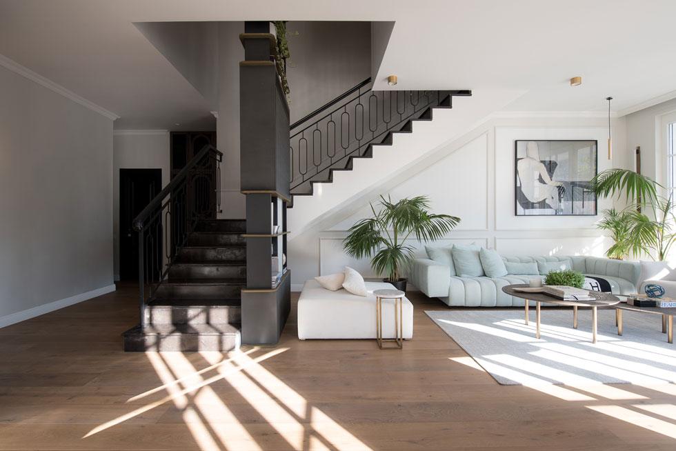 מבט לסלון ולגרם המדרגות שמעליו. קיר הסלון עוטר בפרופילים לאווירה אינטימית ונינוחה (צילום: סיון אסקיו)