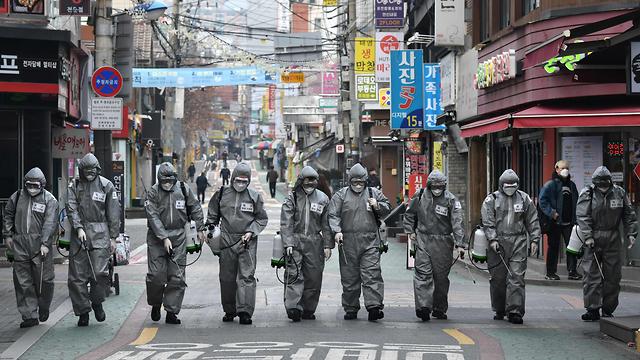 Группа дезинфекторов на улицах Южной Кореи. Фото: AFP