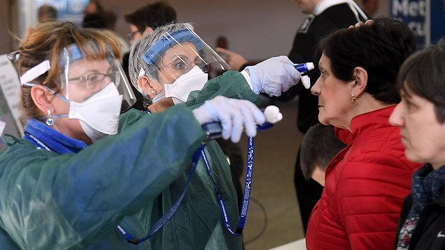 רפואים מודדים חום לאנשים בכניסה ל בית חולים ב פאביה צפון איטליה נגיף קורונה (צילום: EPA)