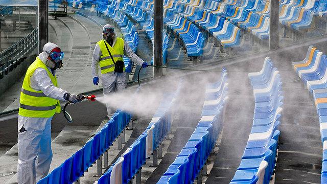 מרססים איצטדיון ב נאפולי איטליה נגיף קורונה (צילום: EPA)