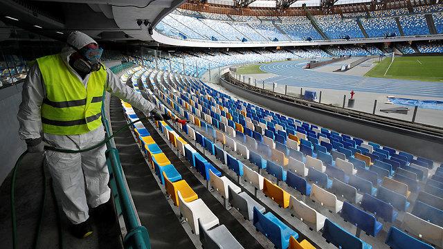 מרססים איצטדיון ב נאפולי איטליה נגיף קורונה (צילום: רויטרס)