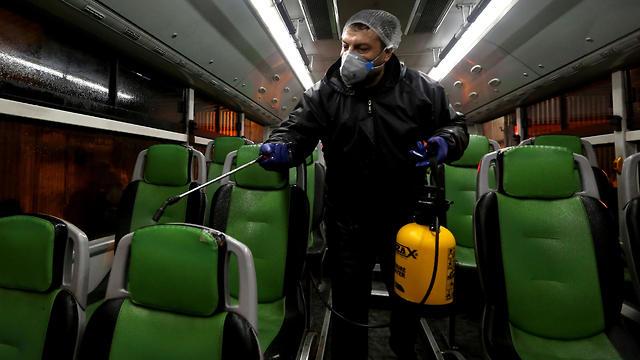 חיטוי וניקוי אוטובוסים איראן (צילום: AFP)