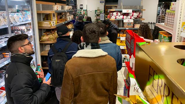 תושבים עומדים בתור בסופר במילאנו (צילום: AFP)