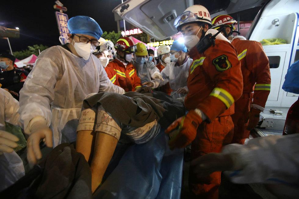 ילד ו אמא חולצו מהריסות מלון למבודדי קורונה שקרס ב סין (צילום: AP)