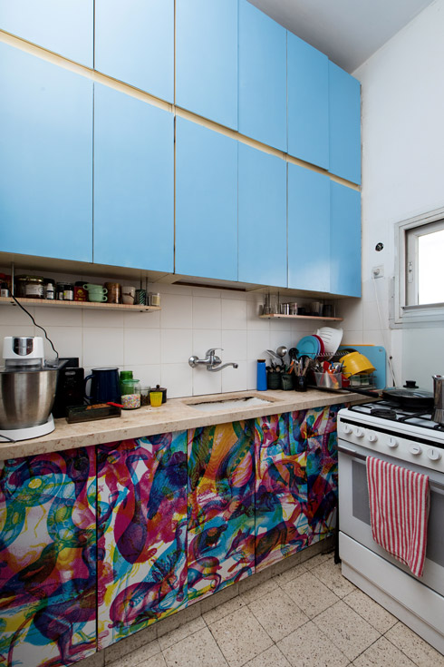 על ארונות המטבח הדביקה טפט שנקנה ממעצב בחו''ל, עם דוגמה שמגיבה אחרת לפילטרים שונים של צבע (בסרטון הווידאו תוכלו להתרשם) (צילום: שירן כרמל)
