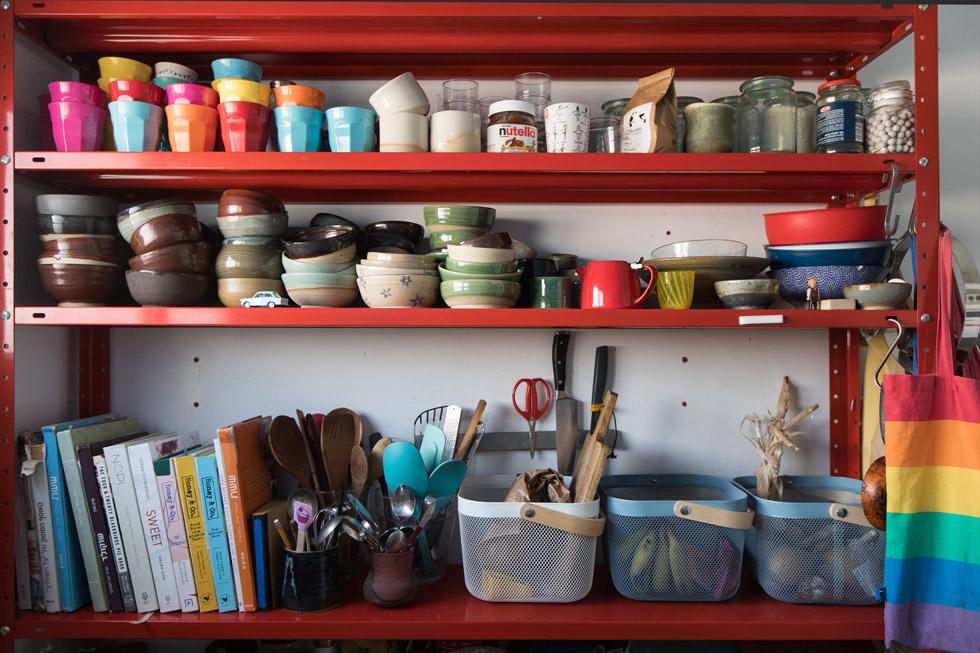 בכל אחד מהחדרים כונניות מתכת פשוטות וצבעוניות. במטבח, למשל, יש ערבוב שמח של כוסות מלמין צבעוניות וכלי קרמיקה, עבודת יד של רותי (צילום: שירן כרמל)