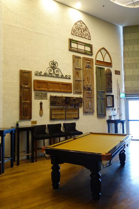 שולחן הביליארד והקולאז' מאחוריו הם עבודה של דן בן אמוץ (צילום: מיכאל יעקובסון)