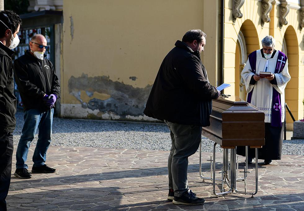 הלוויה לחולה קורונה ליד ברגמו איטליה (צילום: AFP)