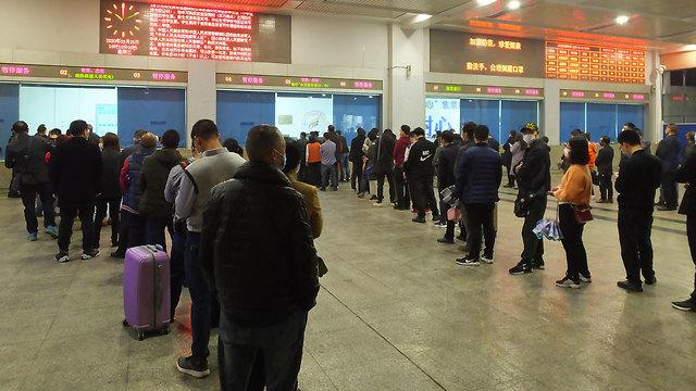 נגיף קורונה מחוז חוביי תחנת רכבת בעיר ייצ'אנג חוזרים לשגרה (צילום: EPA)