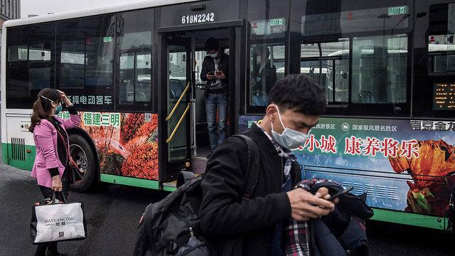 נגיף קורונה מחוז חוביי יורדים מאוטובוס ב ווהאן חוזרים לשגרה (צילום: AFP)
