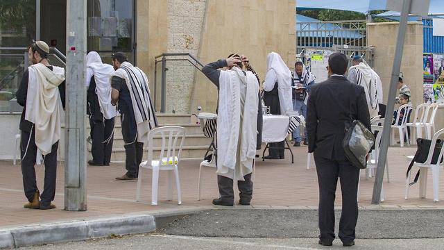 מתפללים ליד בית הכנסת הסגור בנתניה (צילום: עידו ארז)