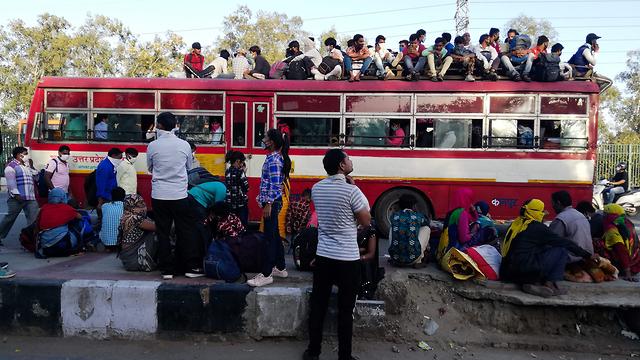 נגיף קורונה הודו מהגרי עבודה תופסים מקום בתור לנסוע הביתה לכפרים בגלל העוצר (צילום: AFP)