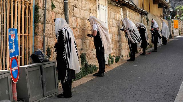 מתפללים ליד בית כנסת סגור ב ירושלים  (צילום: AFP)