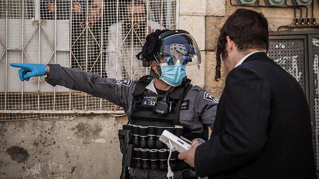 שוטרת מדברת עם חרדי ב מאה שערים ירושלים  (צילום: MCT)