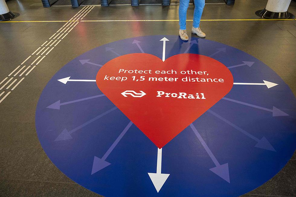 נגיף קורונה הולנד תחנת הרכבת המרכזית אמסטרדם מדבקה לשמור מרחק (צילום: AFP)