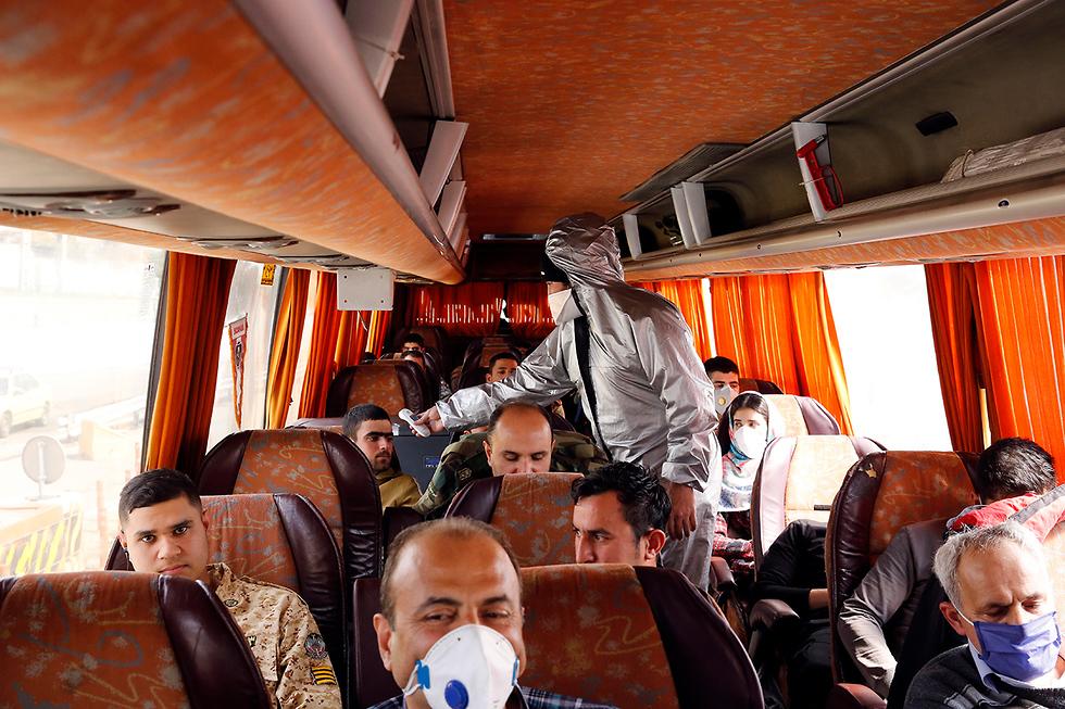 נגיף קורונה איראן איש הסהר האדום בודק נוסעי אוטובוס (צילום: EPA)