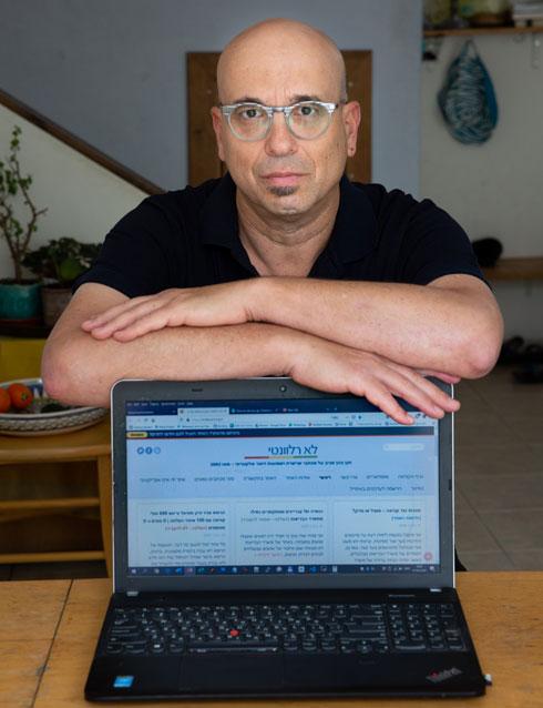 """כהן מציג את האתר שלו. """"אנשים כנראה רואים שאני עושה את העבודה"""" (צילום: אלכס קולומוסקי)"""