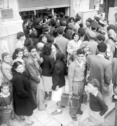 תור מחוץ לחנות בגדים בירושלים בתקופת הצנע, 1950 (צילום: דוד רובינגר)