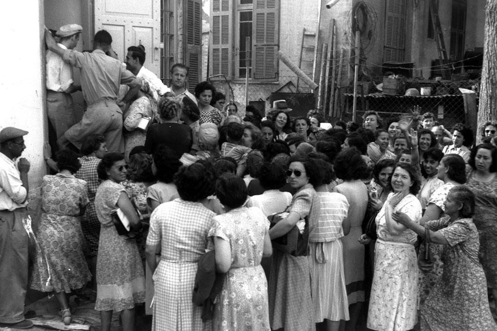 """תור מחוץ לחנות גרבונים בתל אביב, 1951 (צילום: הנס פין, לע""""מ)"""