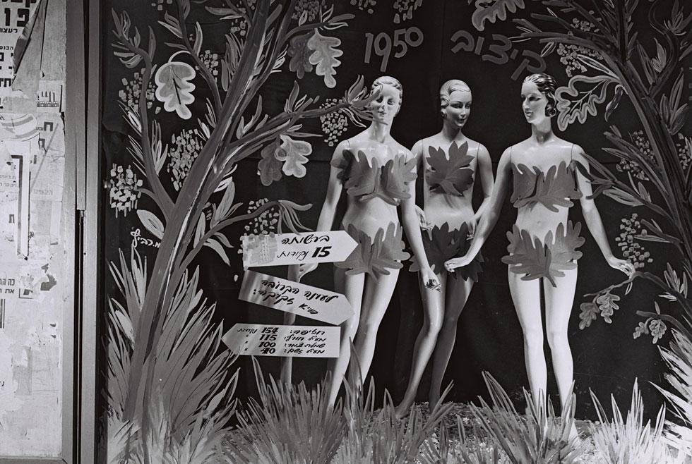 """חלון ראווה מציג את שיטת הנקודות לרכישת בגדים, 1950. """"במדינה בה קיים משטר צנע, בהכרח שאלגנטיות תעלה בדמים מרובים"""", נכתב ב""""ידיעות אחרונות"""" (צילום: טדי ברונר, לע""""מ)"""