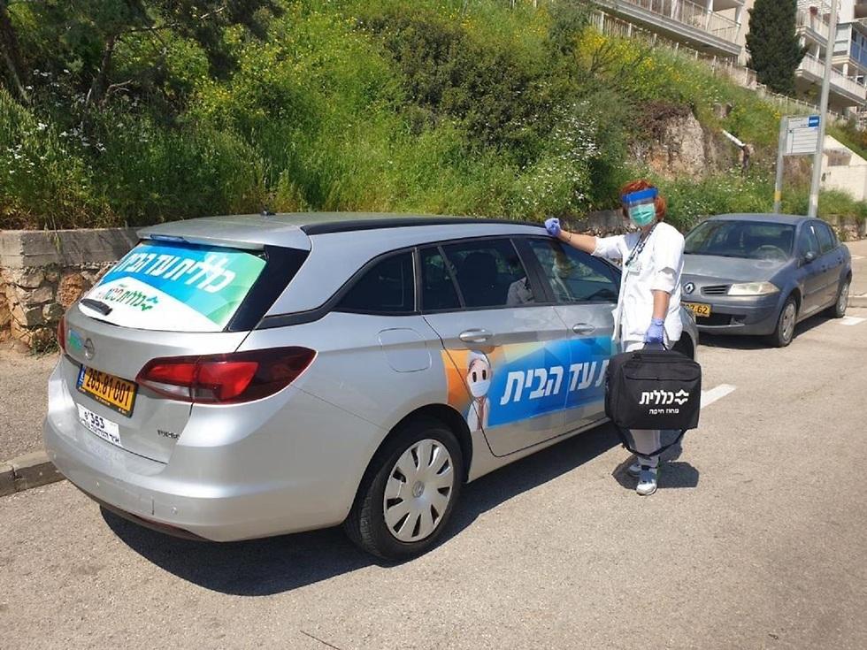 רופאה ליד מכונית בדרך לביקור בית  (צילום: דוברות כללית)