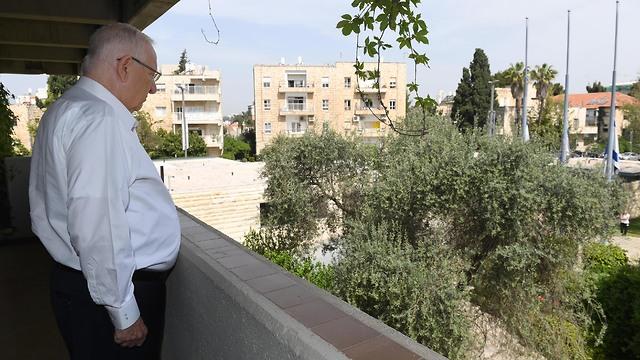 נשיא המדינה ראובן ריבלין עומד במרפסת ביתו במהלך הצפירה  (צילום: מארק ניימן לע