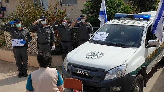 שוטרי השיטור הקהילתי בעמק הירדן הצדיעו במהלך הצפירה לשורדת שואה המתגוררת ביישוב פוריה עילית (צילום: שיטור קהילתי עמק הירדן)