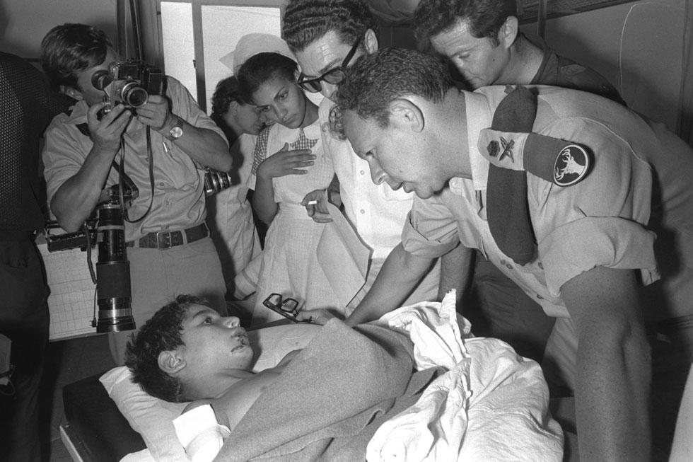 """מוטה גור, שהיה אז אלוף פיקוד צפון, מבקר אצל אחד הילדים הפצועים. """"הזמן לא עושה את שלו באביבים"""" (צילום: משה מילנר, לע""""מ)"""