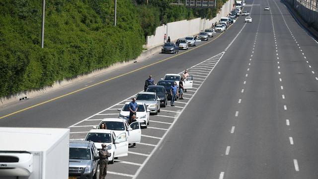 אנשים ורכבים עומדים בצפירת יום הזיכרון בנתיבי איילון (צילום: יאיר שגיא)