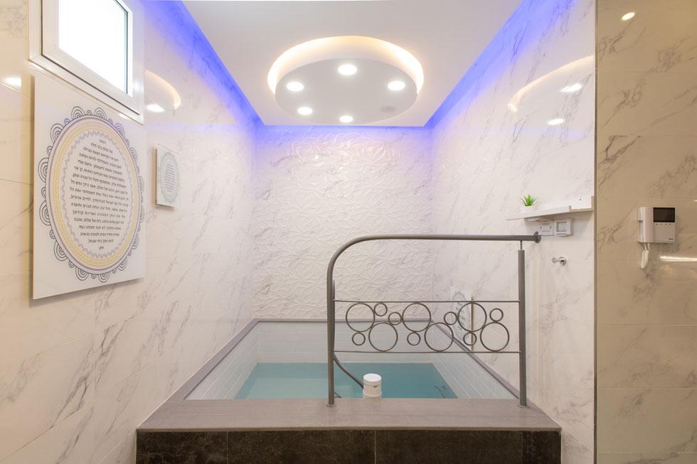 בור טבילה. משמאל כתובה הברכה שנאמרת בטבילה. העיגול בתקרה הוא סימן ההיכר של המעצבת, והוא חוזר במעקה ובעיצוב הברכה התלויה על הקיר (צילום: דור נבו)