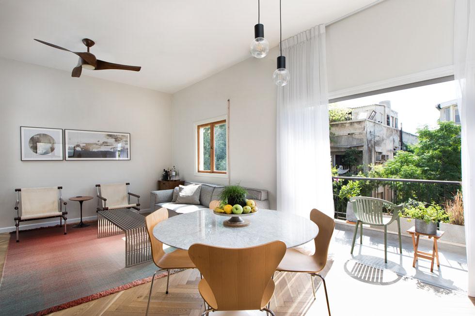 הסלון ופינת האוכל פונים למרפסת קדמית קטנה. הבניין, ברחוב מלצ'ט בלב תל אביב, נבנה מיד אחרי קום המדינה (צילום: שירן כרמל)