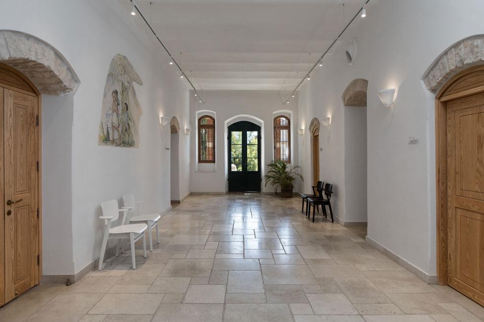 אולם הכניסה וההתכנסות. רצפת האבן חדשה, וכך גם דלתות העץ, שעיצובן הותאם לרוח התקופה. ציור קיר מהמאה ה-19 כוסה בזמן השיפוץ, וניתן לו מקום של כבוד (צילום: שירן כרמל)
