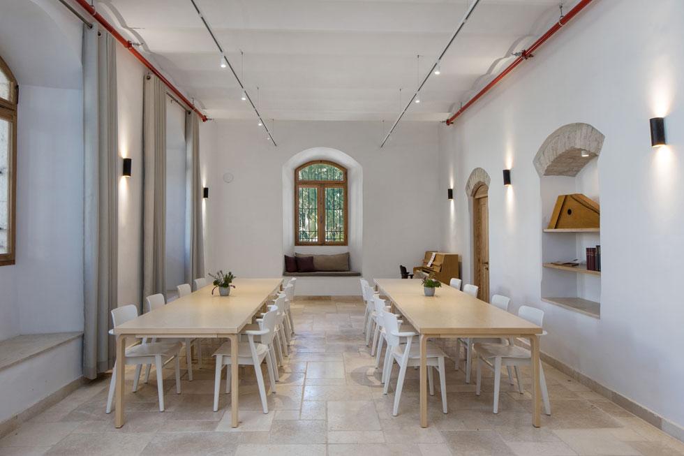 חדר הרצאות שמשמש גם כחדר אוכל. בשונה מאופיה הירושלמי של המעטפת, אומרת מעצבת הפנים יוני פרידמן, ''החלטנו שהחלקים הניידים - ריהוט, תאורה וטקסטיל - יהיו פיניים'' (צילום: שירן כרמל)