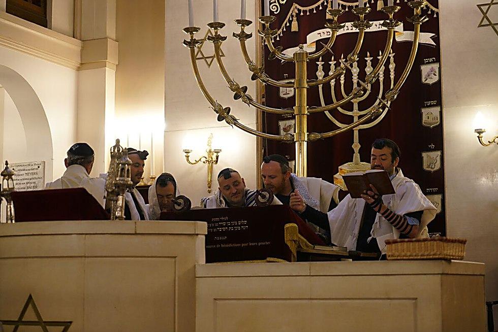 הרב מיכאל אזולאי, שני מימין, קורא בתורה עם אנשי הקהילה בבית הכנסת בניי-סור-סן, פרבר של פריז, ב-11 בדצמבר 2017 (כנען ליפשיץ)
