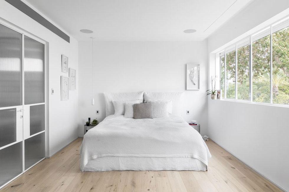 בחדר ההורים, הלבן אינו רק רקע אלא מופיע גם בתמונות, בגופי התאורה ובטקסטיל שעל המיטה. פרקט עץ אלון מעניק לחדר בסיס כהה וחמים יותר (צילום: איתי בנית)