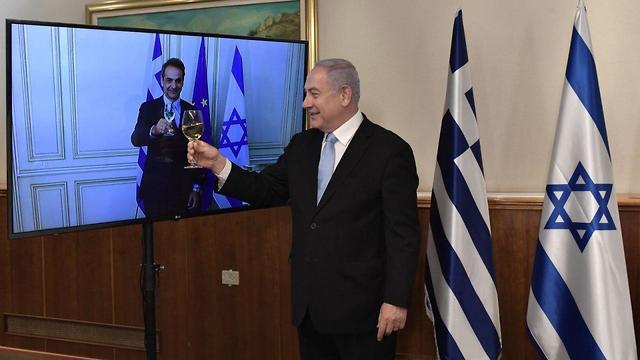 בנימין נתניהו בהרמת כוסית וירטואלית עם ראש ממשלת יוון קיריאקוס מיצוטקיס (צילום: קובי גדעון, לע
